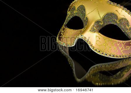 Carnival mask on a black background. The part of mask is reflected by the glass surface