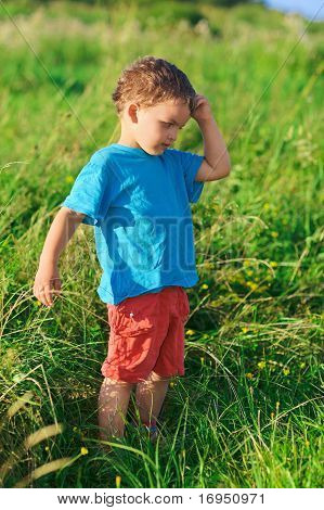 Little Boy Thinking Hard Standing On Green Grass Lawn