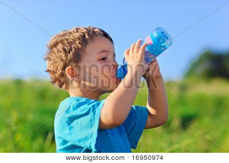 Little Boy Drinking Gas Water On Green Grass Field