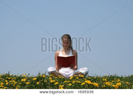Young Woman Reading A Book In A Flowering Field