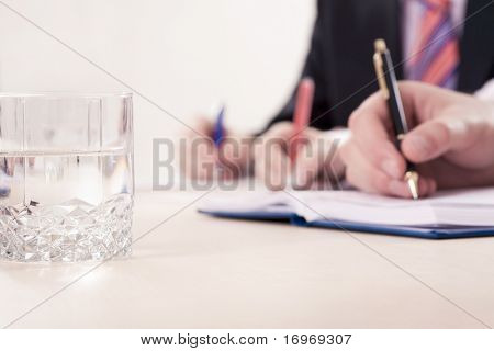 Hands writing notes, focus is on the glass with water