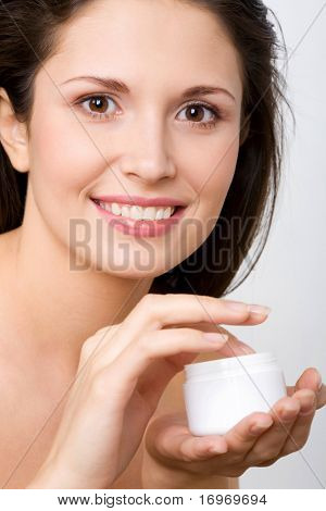 Beautiful woman applying organic cream to her skin