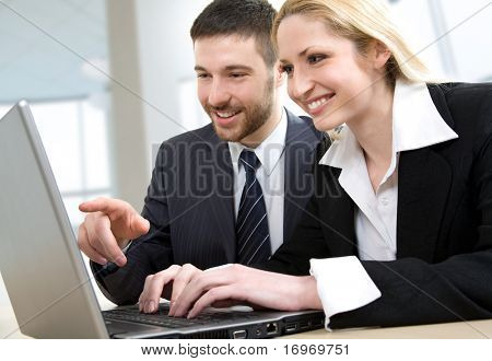 A businessman and a businesswoman at work on the laptop computer