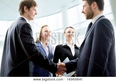Modern businesspeople shaking hands in a modern office