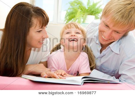 Portrait of happy family reading the book together at home