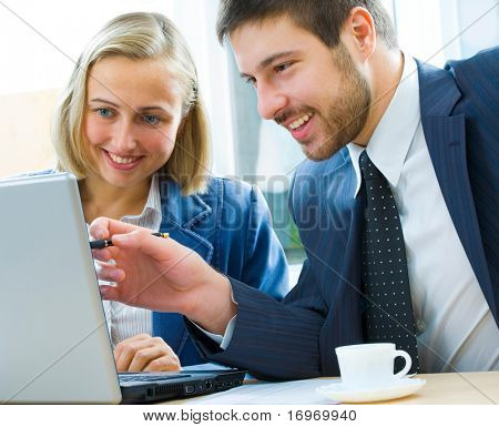Confident manager discussing with colleague a project pointing at laptop