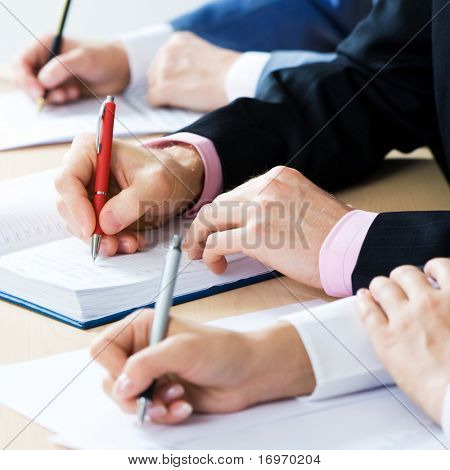 Hands taking notes, focus is on the pen
