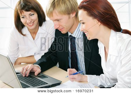 Image of three successful colleagues sitting in office and looking at laptop monitor