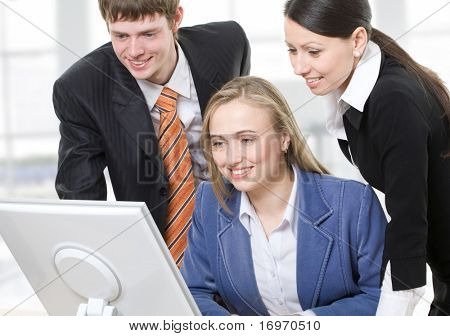 Two businesswomen and one businessman looking at the computer monitor