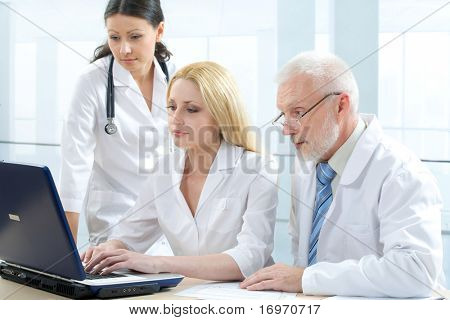 Three medicine workers looking at monitor