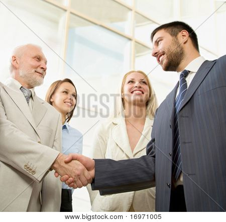 Business people shaking hands in front of a modern office centre