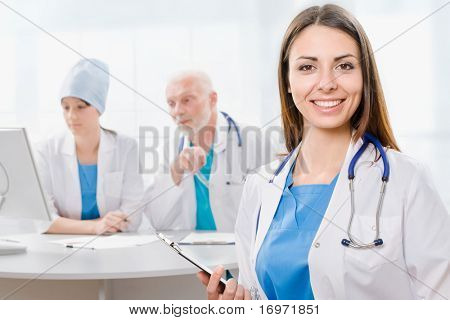 Portrait of a doctor with two of her co-workers sitting  in the background