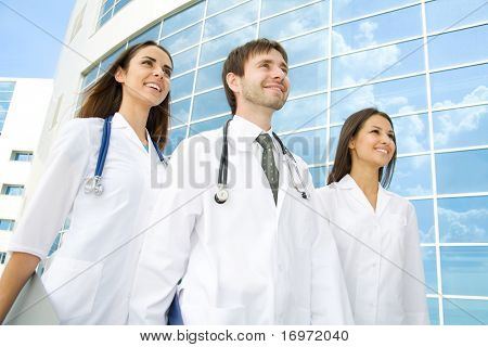 Group of happy young doctors go along a modern building of hospital