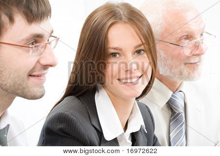 Young businesswoman looking at camera with smile between his colleagues