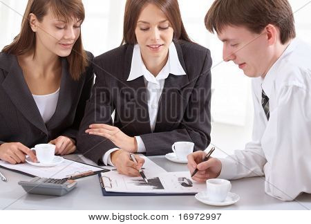 Young businesswoman showing chart his colleagues