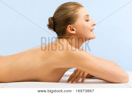 Beautiful woman in spa center on blue background