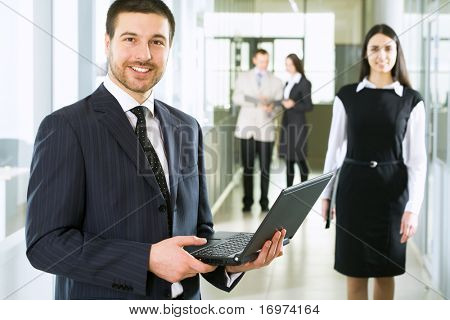 Happy young businessman using laptop in business building,