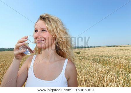 Hermosa mujer rubia, beber agua de vidrio