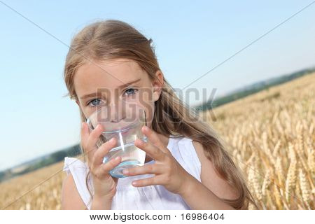Closeup of little blonde girl drinking water