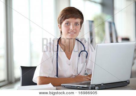 Closeup of beautiful nurse in front of laptop computer