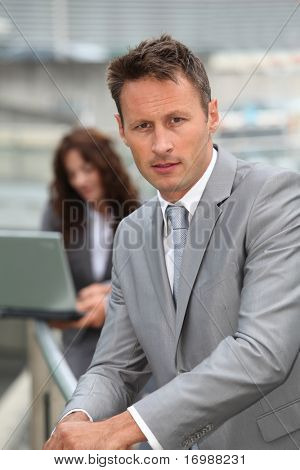 Businessman standing in front of offices outside