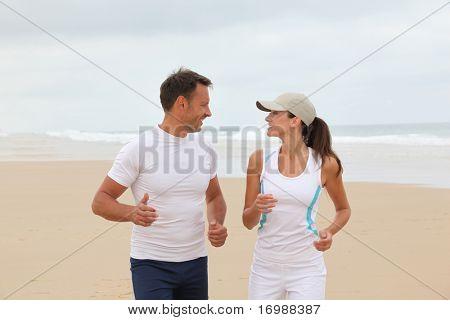 Paar joggen op een zandstrand