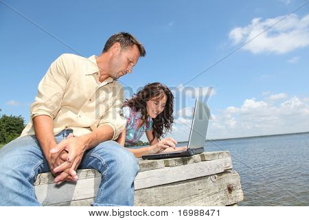 couple using laptop computer on a pontoon