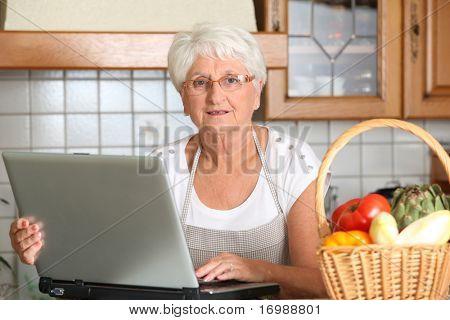 Elderly woman in kitchen with laptop computer