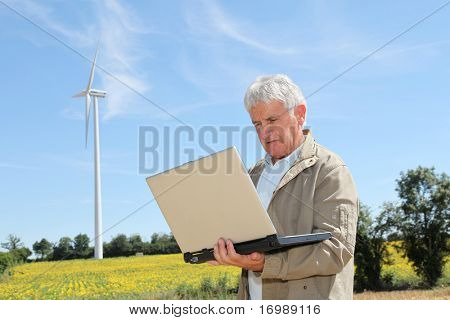 Agronomist in sunflowers field with laptop computer