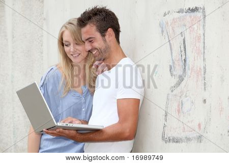 Couple standing against a wall with laptop computer