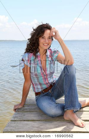 Woman sitting on a pontoon by a lake in summer