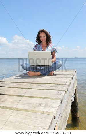 Woman using laptop computer on a pontoon