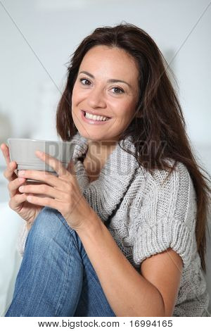 Closeup of beautiful woman with hot drink at home