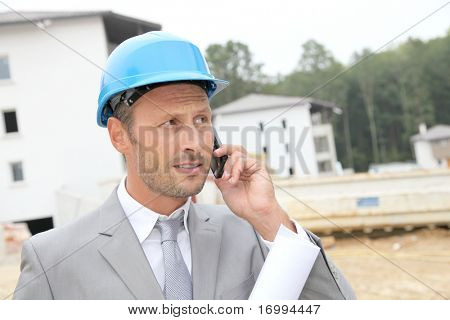 Businessman with helmet checking site under construction
