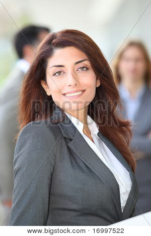 Businesswoman with laptop computer standing outside