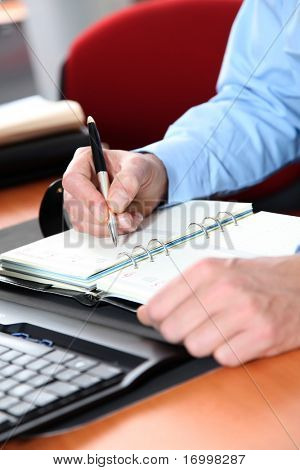 Closeup of man writing on agenda