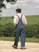 image of tallgrass  - Picture of a farmer in overalls taking a stroll at the Tallgrass prairie National Preserve in Chase County Kansas - JPG