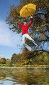 Постер, плакат: забавный парень летит с желтый зонтик над озером