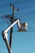 stock photo of cherry-picker  - Cherry picker raised up to power lines - JPG