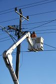 stock photo of cherry-picker  - Worker in cherry picker fixing power lines - JPG