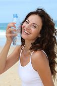 foto of drinking water  - Beautiful woman drinking water at the beach - JPG