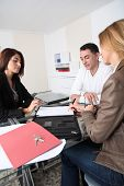 image of real-estate agent  - Couple signing property contract with real estate agent - JPG
