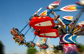 picture of carnival ride  - Carnival Ride with motion blur against a colorful blue sky - JPG