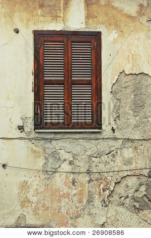 Old  shuttered window on the dilapidated building