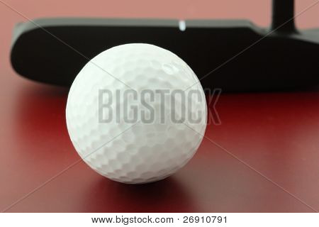 golf ball on red surface and club