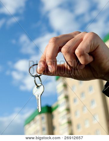 hand holding keys, house in the background