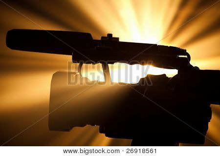 silhouette of professional video camera
