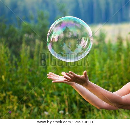 hand catching a soap bubble