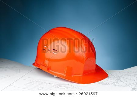 orange hard hat on the construction plan against blue background