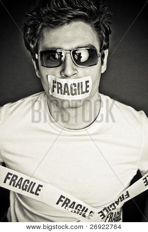 artistic  portrait of brunette man with the glasses covered fragile tape